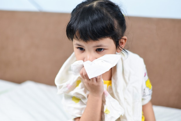 Asian little girl sick wrapped in handkerchief get cold and blow nose the flu season, child runny nose and sneezing blowing their nose and fevers at home