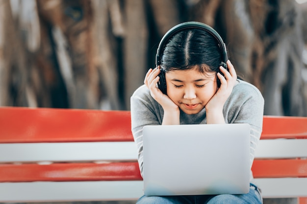 Asian little girl siting and listen to music