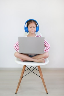 Asian little girl sitting on chair using headphone study online learning class by laptop