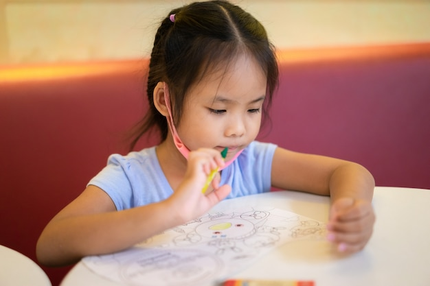 Asian little girl sitting at table, drawing pictures with colored pencils in paper at home