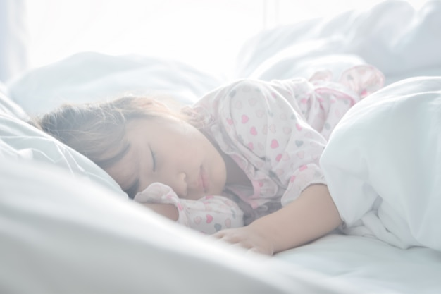 Asian little girl sleeping in the bed on the morning time with sunrise light soft focus