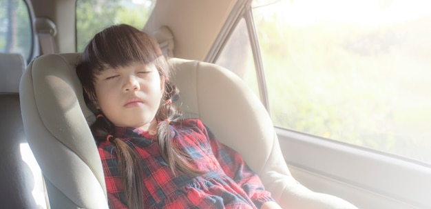 Asian little girl sleeping in car with car seat