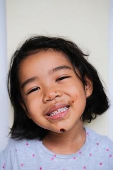 더러운 입으로 아이스크림을 먹고 행복한 미소를 짓고 있는 아시아 소녀