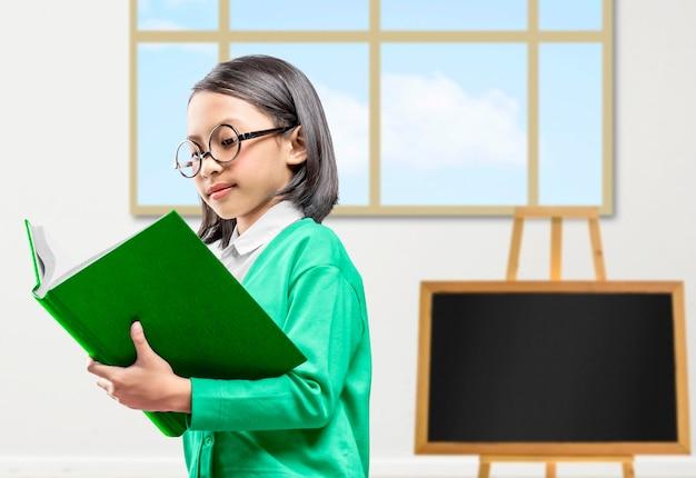 立って教室で本を読んでいるアジアの少女。学校に戻るコンセプト。