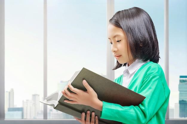 立って家で本を読んでいるアジアの少女。学校に戻るコンセプト。