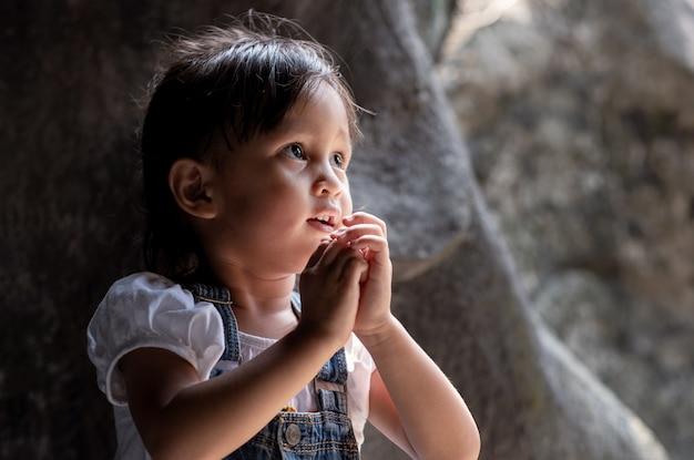 Asian little girl standing in the little cave and pray and looking up to the light