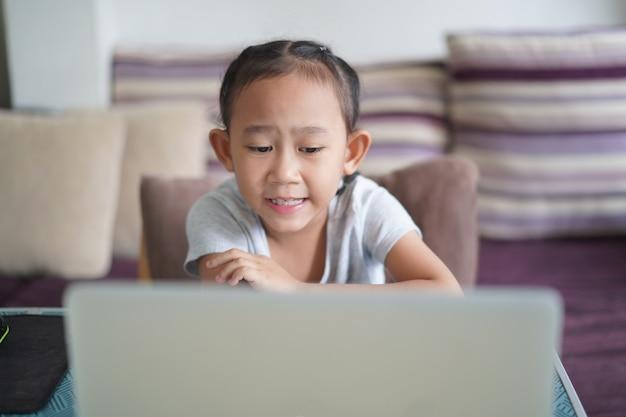 Азиатская маленькая девочка изучает домашнее задание онлайн-урок, концепция идеи социального дистанционного онлайн-образования
