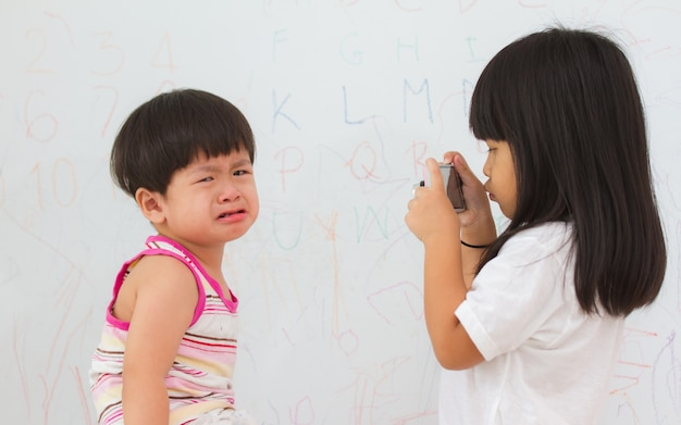 Asian little girl take a picture crying little boy.