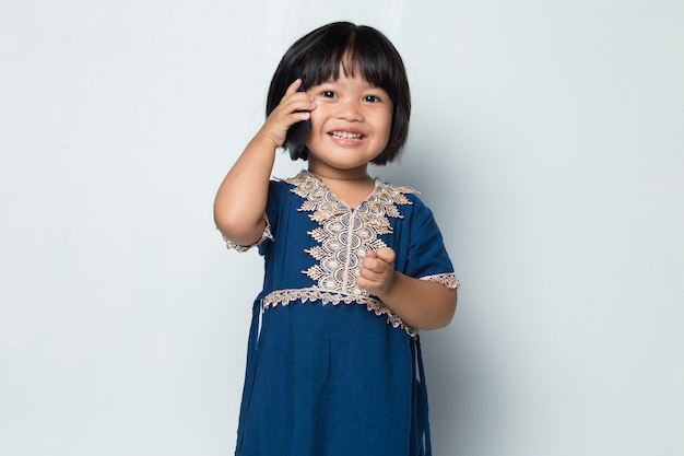 Asian little girl using smart phone on white background
