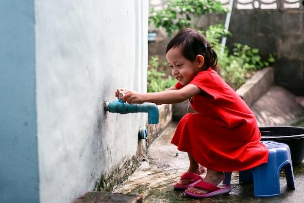 手を洗って家で閉じるアジアの少女