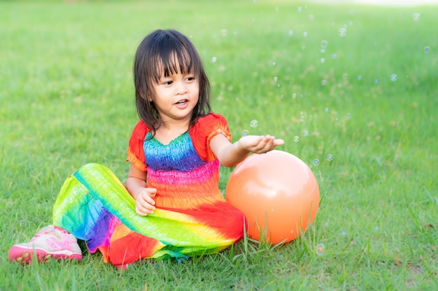 Asian little girl wear colorful dress is playing the soap bubbles in the park