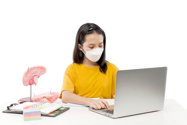 흰색 배경에 격리된 온라인 학교 수업에 참석하는 노트북으로 마스크를 쓴 아시아 소녀. 검역 중 온라인 교육
