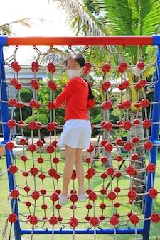 屋外の登山ロープネットで遊んでいる間保護マスクを身に着けているアジアの少女。背面図