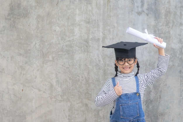 Asian little girl wearing a graduation cap and holding diploma on white background