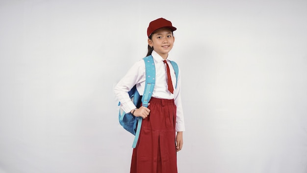 孤立した白い背景で幸せに笑って帽子とランドセルを身に着けているアジアの少女