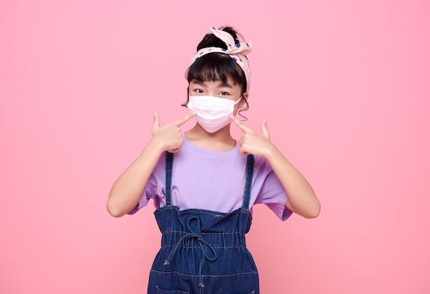 분홍색 벽에 고립 된 바이러스 covid-19로부터 그녀를 보호하기 위해 마스크를 쓰고 아시아 소녀.