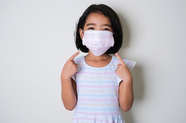 Азиатская маленькая девочка в защитной медицинской маске и ее пальцы, указывающие на нее