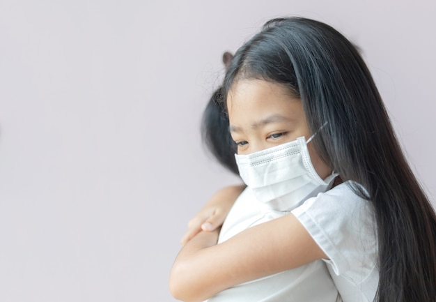 Asian little girl wearing a protective medical mask hugs her mom