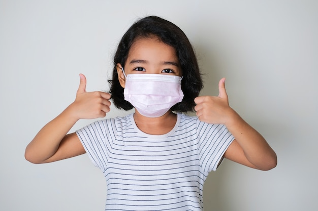 Asian little girl wearing protective medical mask while giving two thumbs up