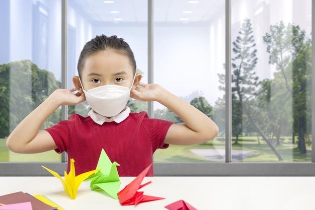 Азиатская маленькая девочка в маске дома