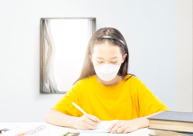 Азиатская маленькая девочка в маске делает домашнее задание дома. онлайн-обучение во время карантина