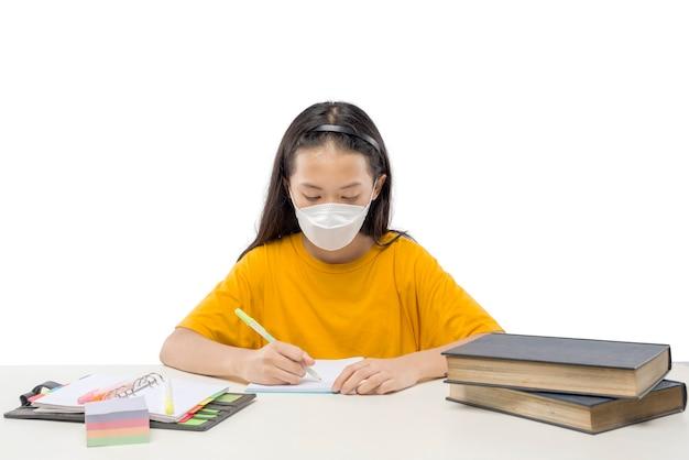 白い背景で隔離の宿題をしているマスクを身に着けているアジアの少女