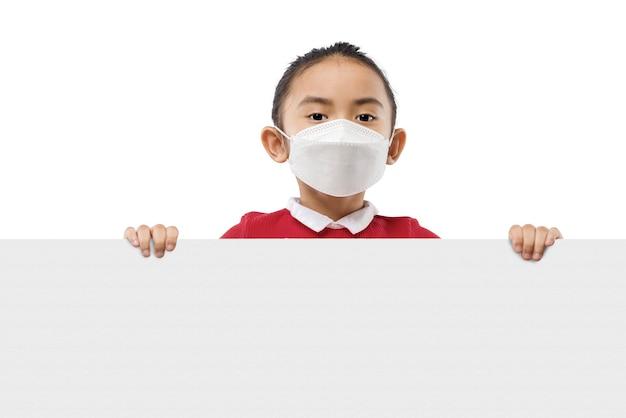 白い背景の上に分離された空のボードを保持しているマスクを身に着けているアジアの少女