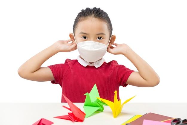 白い背景で隔離のマスクを身に着けているアジアの少女
