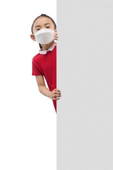 白い背景で隔離の壁の横に立っているマスクを身に着けているアジアの少女