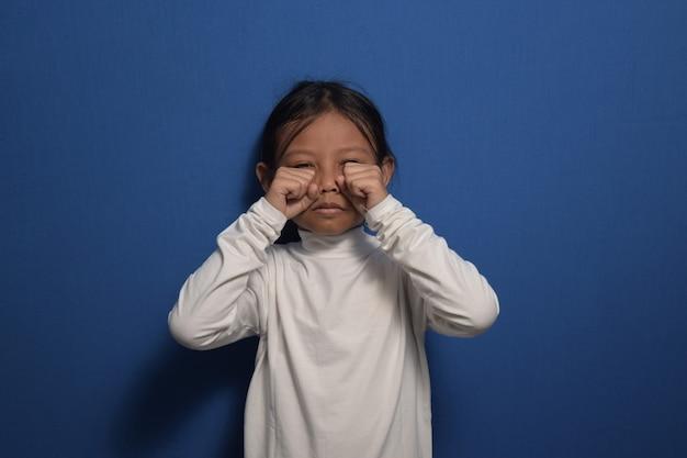 흰색 티셔츠를 입고 울고 손으로 눈을 비비는 아시아 소녀