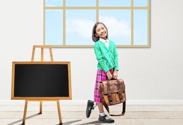教室でバッグを持つアジアの少女。学校に戻るコンセプト