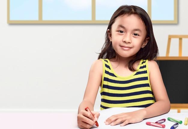 テーブルの上の紙にクレヨンで描いているアジアの少女。学校に戻るコンセプト