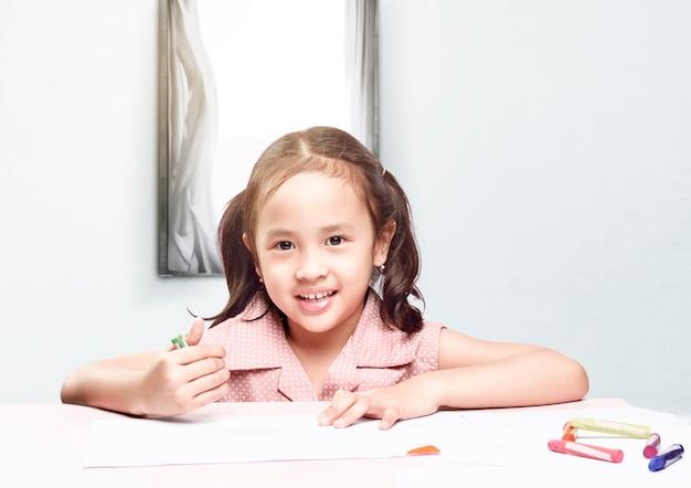 Азиатская маленькая девочка с карандашным рисунком на бумаге на столе. снова в школу концепции