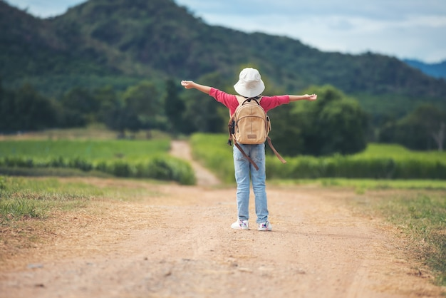 Asian little girl with backpack walking at natural park outdoor forest and mountain background. travel environment education lifestyle healthy concept
