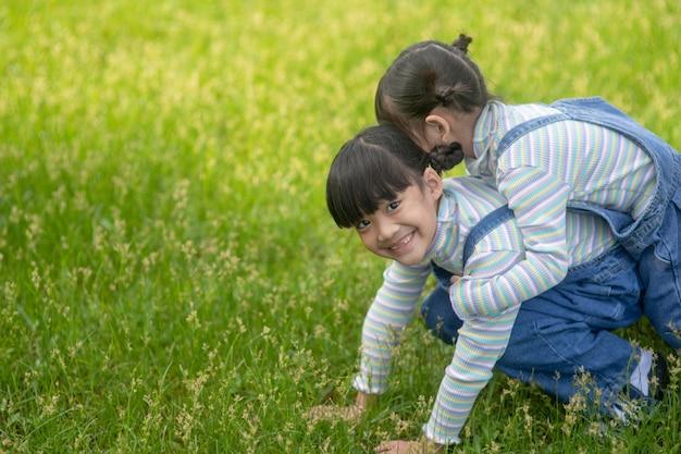 그녀의 뒤에 타고 공원에서 언니와 아시아 어린 소녀