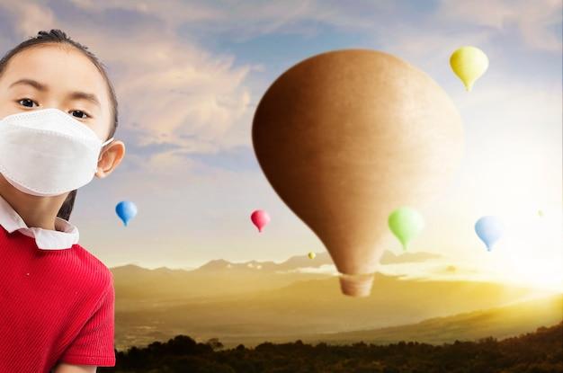 夕焼け空の背景で飛んでいるカラフルな気球とフェイスマスクを持つアジアの少女