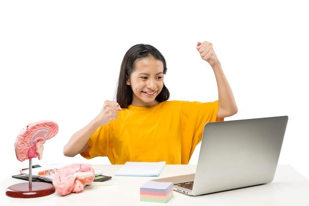Азиатская маленькая девочка с ноутбуком, посещая школьный класс онлайн, изолированные на белом фоне. онлайн-обучение во время карантина