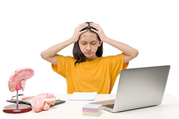 Азиатская маленькая девочка с ноутбуком, чувствуя стресс для онлайн-школьного класса, изолированного на белом фоне. онлайн-обучение во время карантина