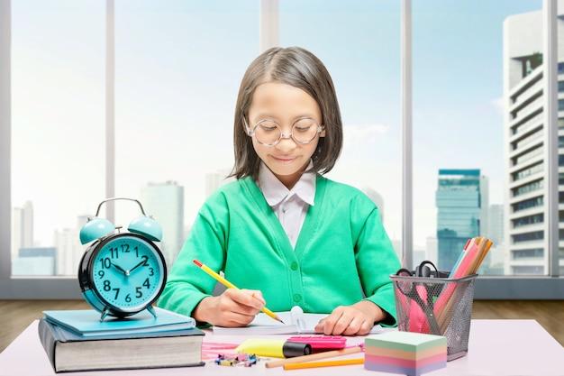Азиатская маленькая девочка с стационарными пишет в книге на столе. снова в школу концепции