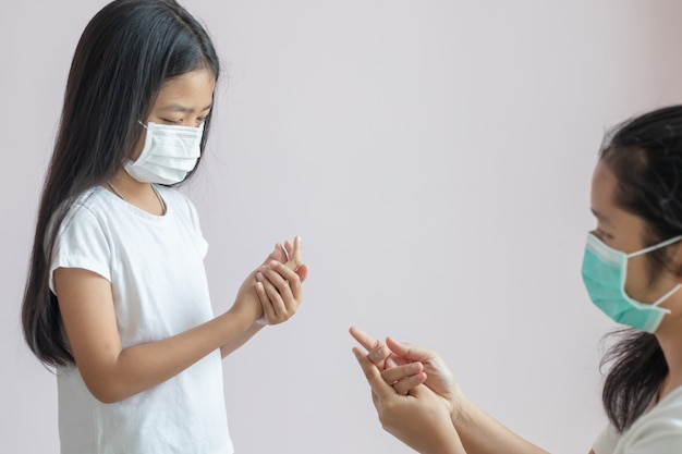 Asian little girl and a woman wears a protective medical mask