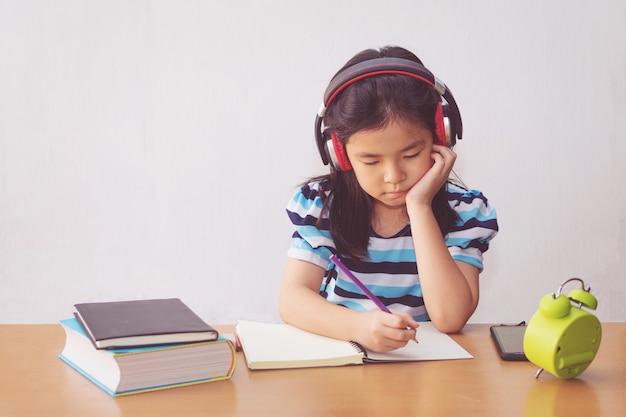 本と音楽を聞くヘッドフォンを書くアジアの少女。