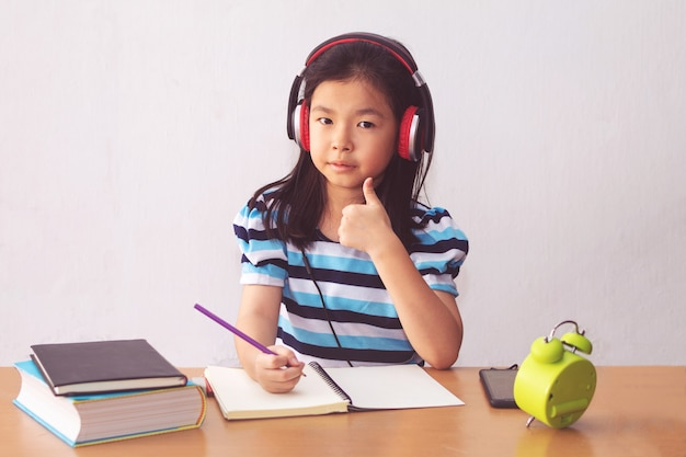 Asian little girl writeing a book and headphones listening to music.