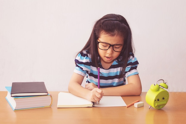 Asian little girl writeing a book on table