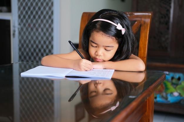 Азиатская маленькая девочка, пишущая на книге