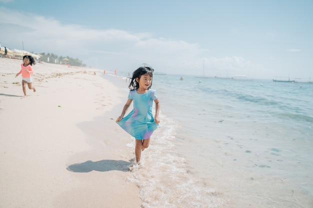 Asian little girls run and laugh in the beach