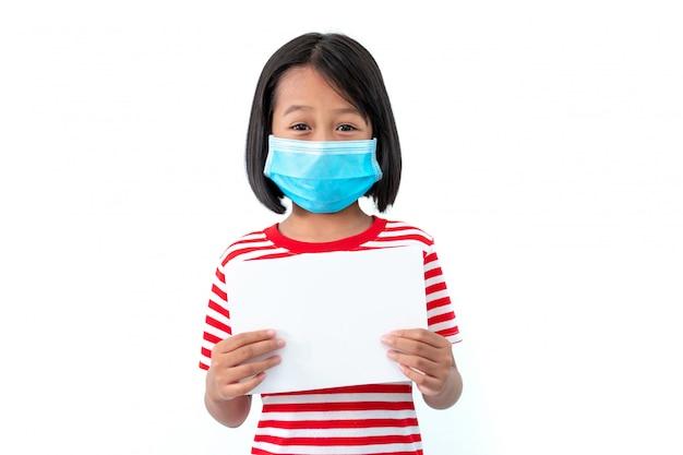 白の空白の白い紙でコロナウイルスcovid-19の広がりを防ぐためにマスクを着ているアジアの女の子