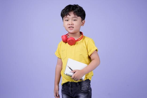音楽を聴いてヘッドフォンでアジアの小さなハンサムなかわいい男の子