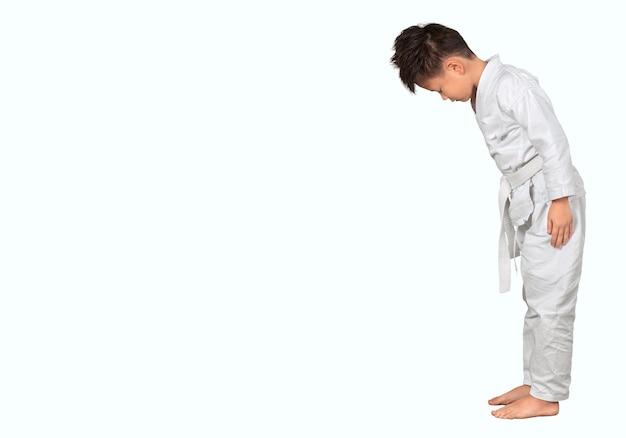 Азиатский маленький мальчик каратэ в белом кимоно на фоне