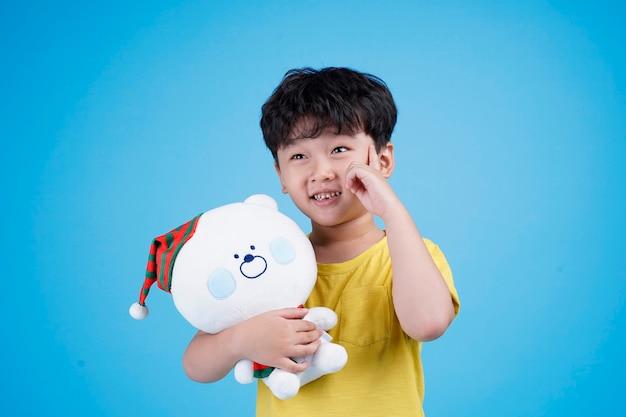 テディベア人形を持って抱き締めるアジアの小さな子供の男の子