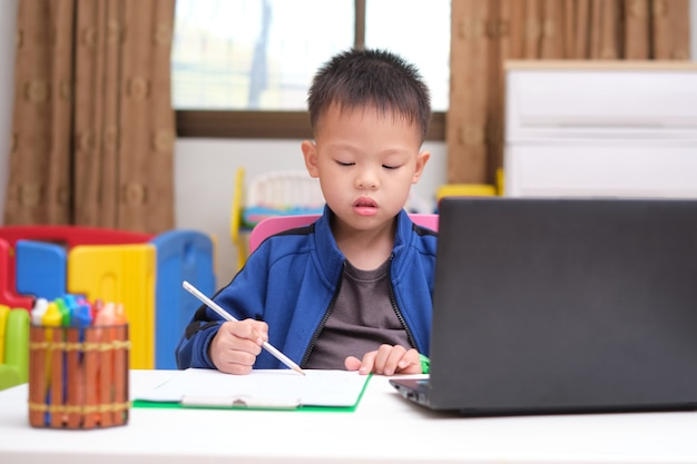 Asian little kid drawing and using laptop computer studying homework during his online lesson at home